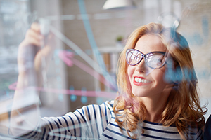 woman in glasses drawing graphs on glass wall
