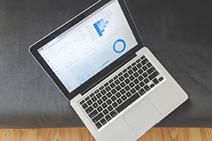 silver laptop open with blue financial charts and various statistics on a black surface