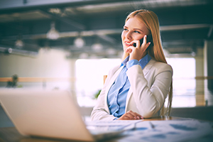 Young female agent speaking to client on the phone in office