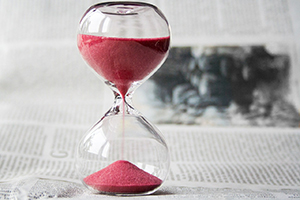 hourglass with red sand against newspaper background