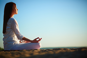 woman in white shirt and pants sitting and meditating with clear blue sky in the background