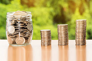 coins in jar and three stacks of coins arranged in increasing manner
