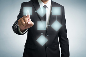main in suit pointing at digital flow chart